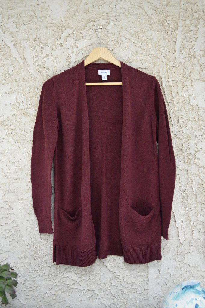 Image of cardigan sweater on a hanger with arms hanging down. Try avoid hanging knit items this way